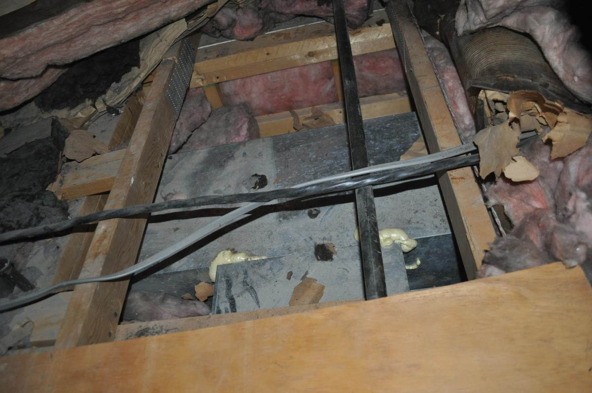 Insulation is set aside to reveal an open soffit in the attic