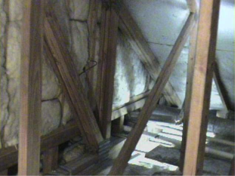 The floor cavities under this attic kneewall are completely open to the unconditioned attic space and a prime target for wind washing
