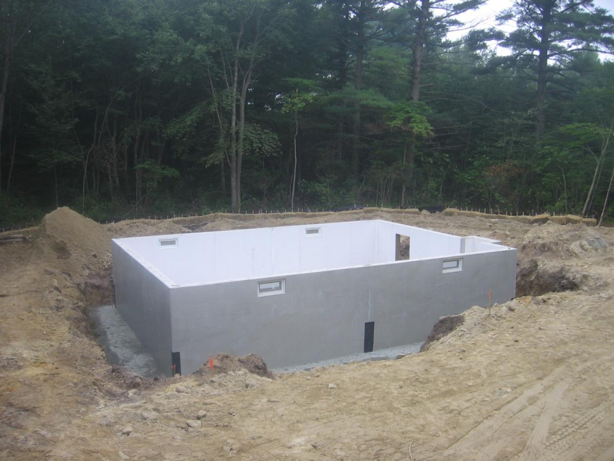 A precast insulated concrete panel foundation is set in place on a base of crushed rock