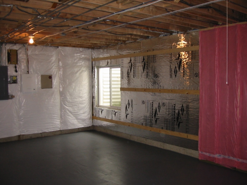 Foil-faced polyiso foam is held in place along the interior of a basement wall with nails or screws through the furring strips. Seams are sealed with foil tape and all edges are sealed with caulk or foam