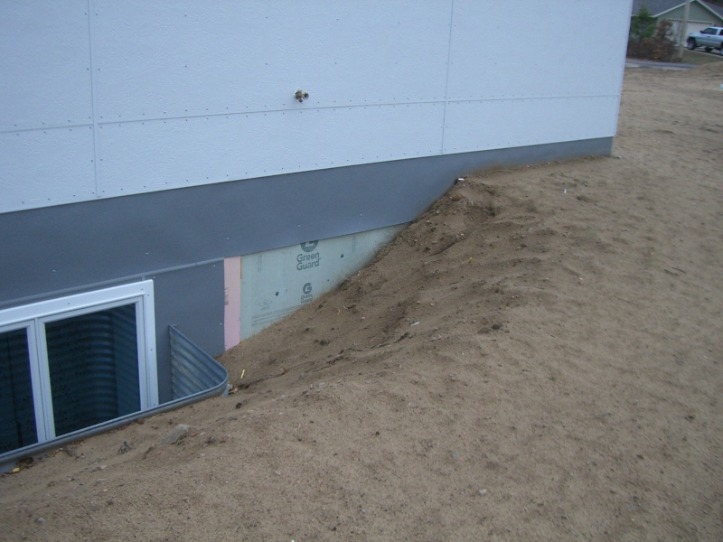 Rolled fiberglass sheets are installed to protect exterior XPS at and above grade