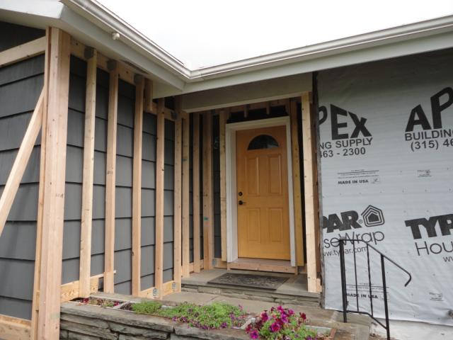 exterior spray foam sealant. ledger board, metal brackets, and vertical 2x4s have been installed in preparation for exterior spray foam sealant