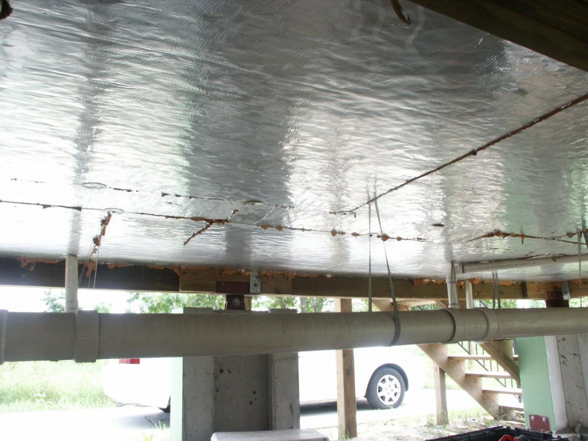 Foil-faced polyisocyanurate insulating rigid foam sheathing is installed below the floor framing of this house built on piers