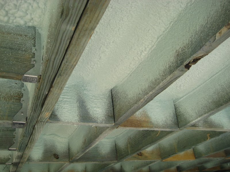 Spray foam insulation air seals the underside of the flooring of a home built on piers