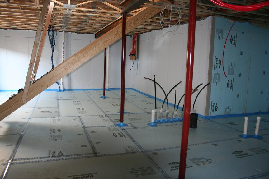 Rigid foam insulation is installed over a drainage pad of aggregate to serve as a capillary break under the basement slab. Seams and pipes are sealed with tape and gaskets so foam can serve as a continuous vapor barrier as well.