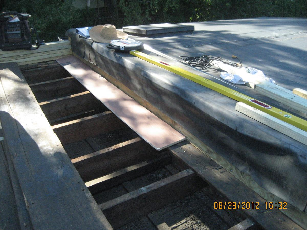 A strip of OSB sheathing is installed along the perimeter when retrofitting a flat roof with a parapet