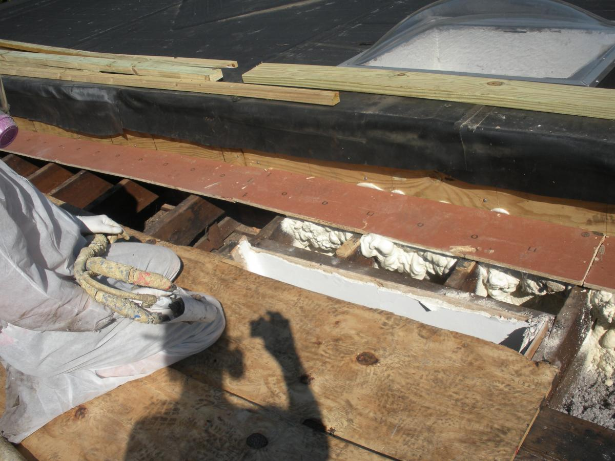 Closed-cell spray foam fills the roof joist cavities forming an air barrier between the masonry parapet wall and the roof sheathing