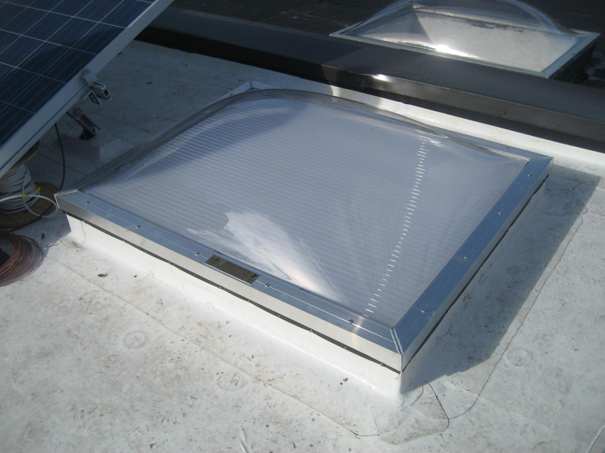 Strips of roofing membrane are used to flash around a skylight on a flat roof retrofit.