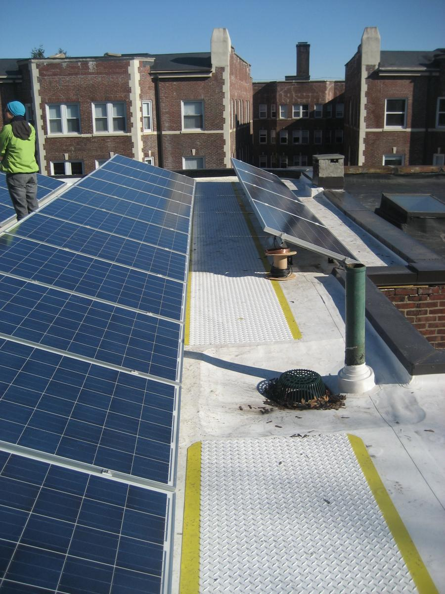 The retrofitted flat roof has PV panels and walking mats installed over the roofing membrane