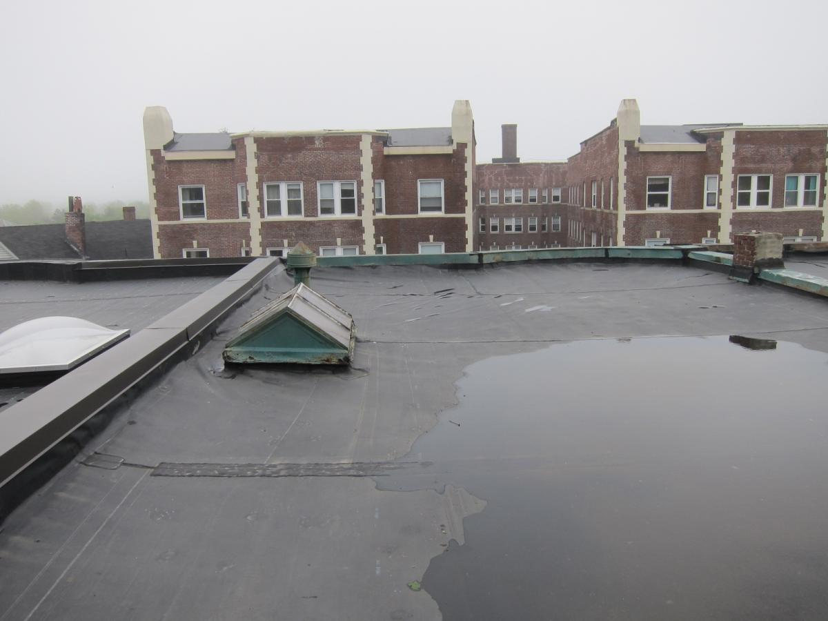 The existing flat roof before removal of membrane shows lack of slope allowing water to pool on the surface