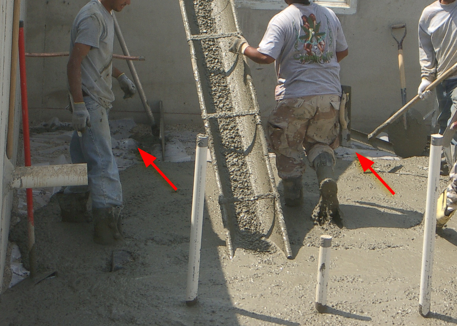 Here the polyethylene sheeting can still be seen as cement is poured to create the foundation. Care must be taken when walking on the sheeting to ensure it does not tear or pull apart at the seams