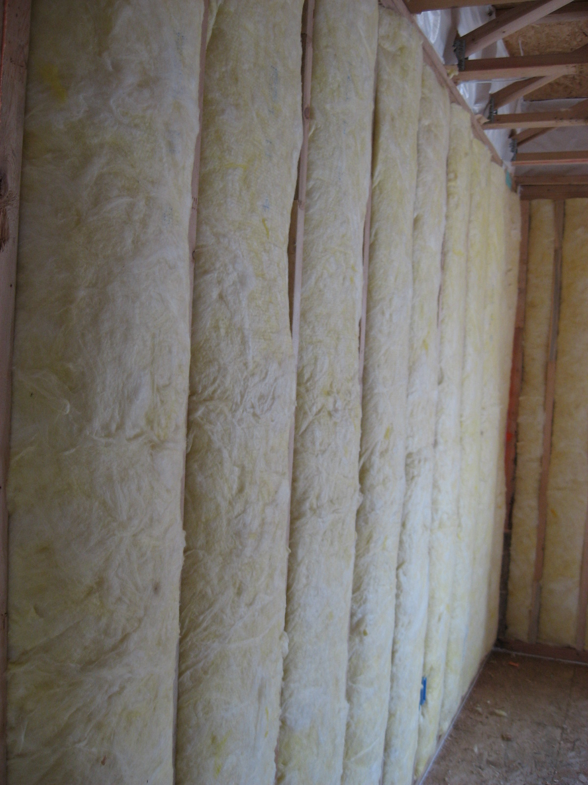Unfaced fiberglass batt insulation is installed to completely fill the wall cavities