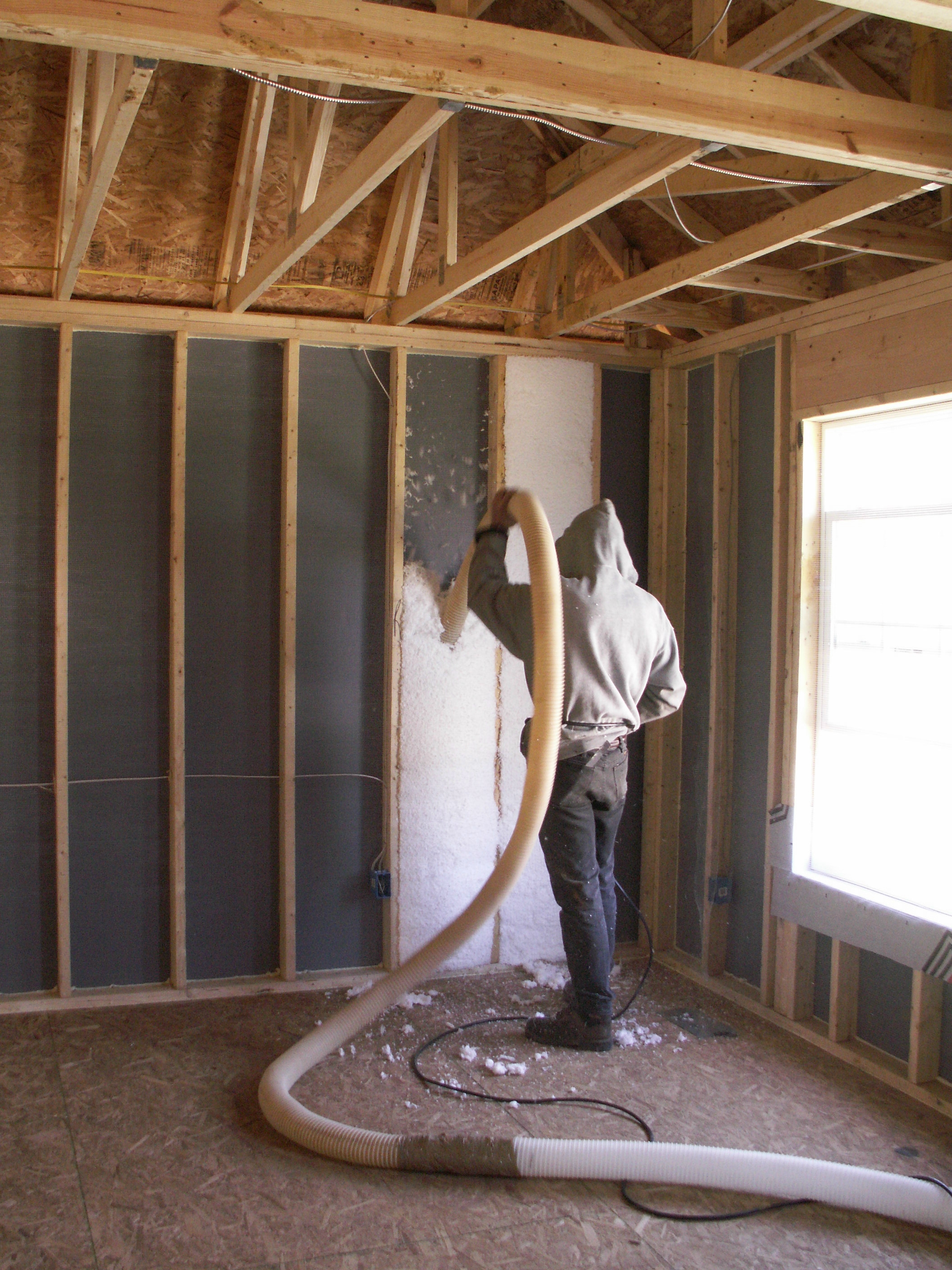 Blown fiberglass insulation fills netted wall cavities