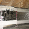 Right - This unvented crawlspace is insulated along the walls and between the floor joists with 2-inch foil-faced polyisocyanurate; a termite inspection gap is visible above of the wall insulation and below the band joist.