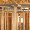The drywall above the dropped ceiling duct chase extends beyond adjoining top plates for a continuous air barrier