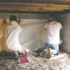 Right - Technicians use adhesive when installing the vapor barrier along the walls of this crawlspace.