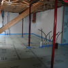 Rigid foam insulation is taped at seams and installed over a drainage pad of aggregate to serve as a capillary break under the basement slab.