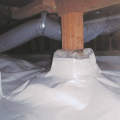 Right - A foundation post is wrapped with vapor retarder which also covers the floor of this crawl space.