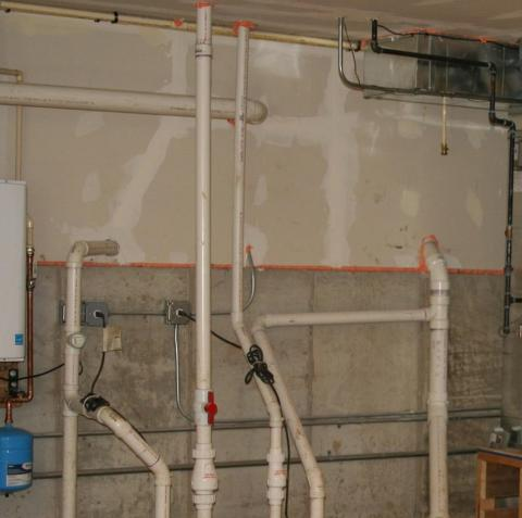 The sump pumps in this basement are covered with gasketed lids to keep soil gases out of the home.