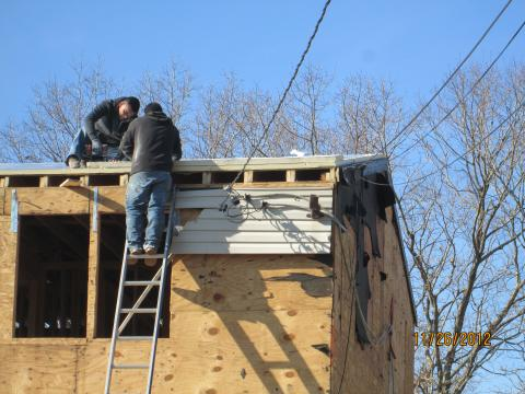 The existing 2x8 roof rafters were topped with OSB; two layers of 2-inch rigid foam; plywood; ice and water shield at rakes, eaves, and valleys; underlayment; and fiberglass shingles, plus 6 inches of open-cell foam under the decking.