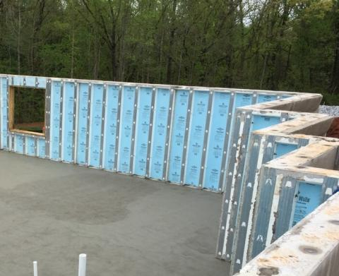 Precast concrete basement walls come to the site with integrated rigid foam insulation and steel-faced concrete studs.