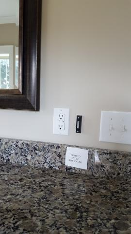 A push button operates the on-demand hot water circulation pump in this master bathroom.