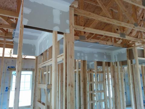 Drywall is installed before framing in dropped soffits to provide an air barrier above these duct chases.