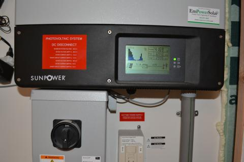 The photovoltaic system comes with a readout screen showing power production.