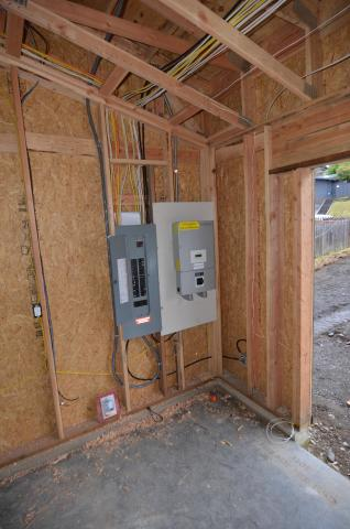 Wall space is provided next to the electrical panel in the garage for the home's photovoltaics system.