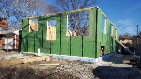 A coated OSB product with taped seams covers the walls to serve as both sheathing and weather-resistant barrier.
