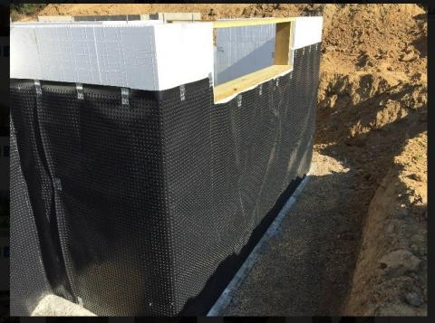 A dimpled plastic water barrier protects the insulated concrete form basement walls and carries any ground water down the walls to the footing drain to minimize the opportunity for water intrusion and frost heave.
