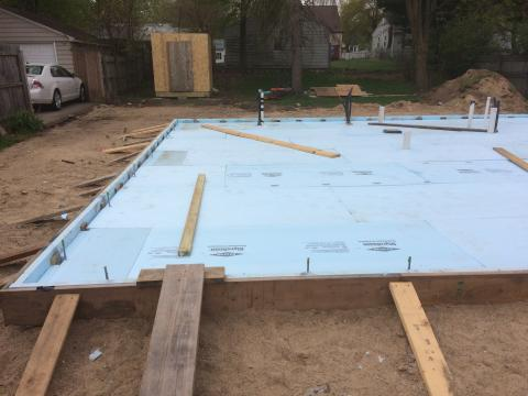 Rigid foam extends under the full slab and lines the inside edges of the foundation walls.