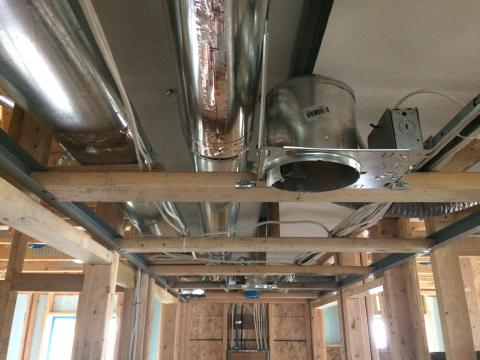 Drywall is installed as an air barrier above the central hallway duct chase prior to installing the trunk ducts.