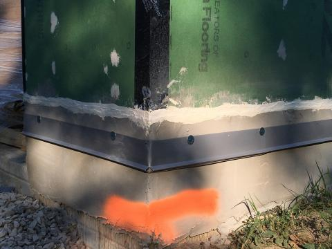 Flashing is installed above the foundation wall before installing the siding. Seams in sheathing are sealed with tape and caulk, while nail holes are sealed with caulk.