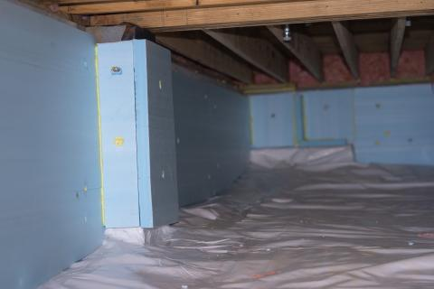 A vapor barrier was installed on the floor of this crawlspace and extended up the walls then the foundation walls were covered with rigid foam.