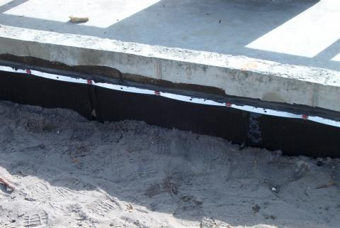 A below-grade foundation wall with a damp-proof coating