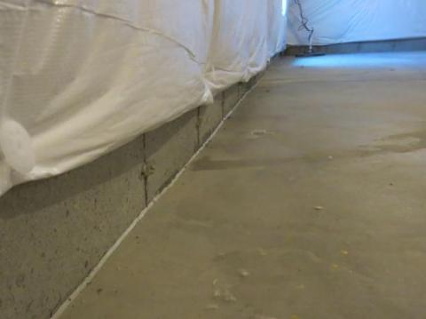 Caulk the seam between the slab and foundation wall