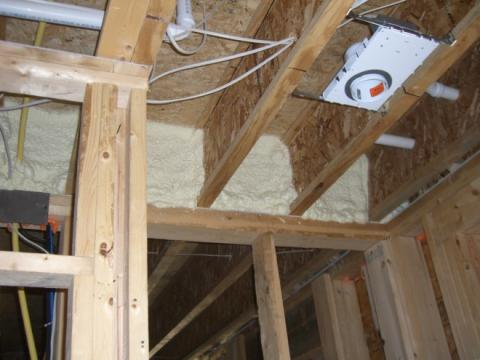 Right – Closed-cell spray foam insulates and air seals the rim joist above a shared wall between the garage and living space