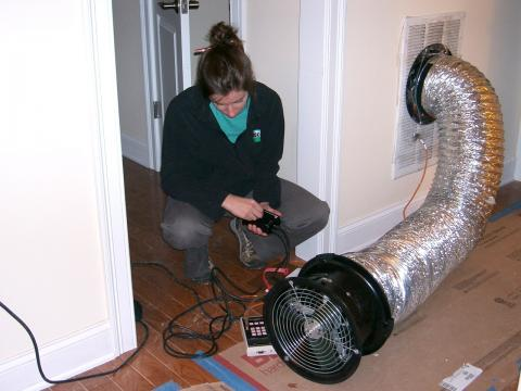 A technician conducts a duct blaster test