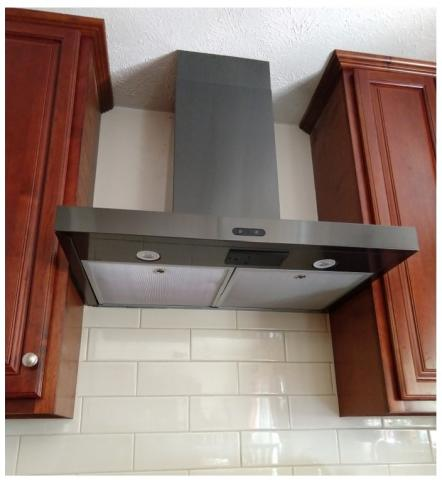 This ducted, wall-mounted range hood exhaust fan replaced a recirculating fan that did not adequately remove kitchen contaminants.