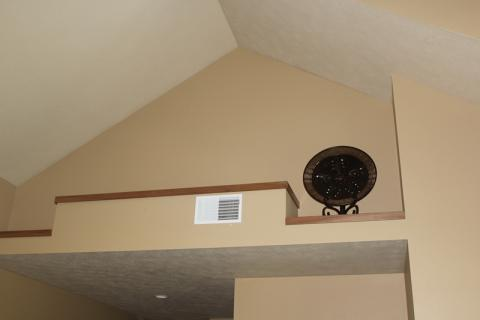 A ductless heat pump is hidden behind a wall outcropping above the hallway ceiling.