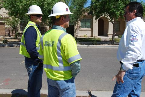 A builder meets with utility staff at a job site.