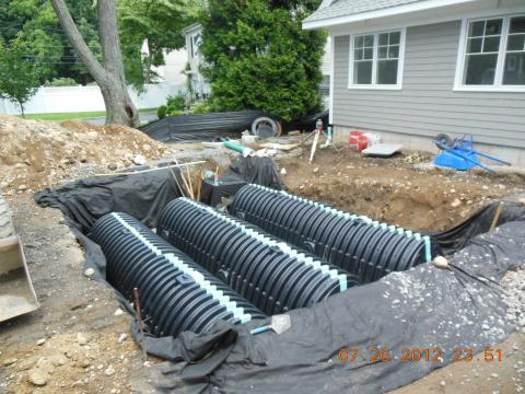 A storm water management system channels rainwater to retention chambers buried in the front yard.