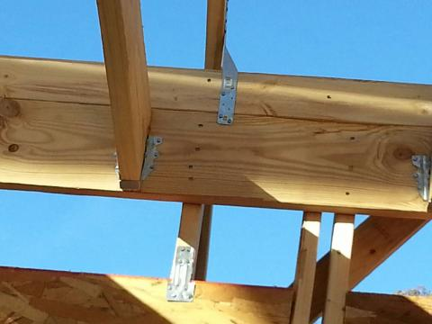 Bolted metal hurricane strapping ties the roofing to the framing and the framing to the foundation walls for resistance to high winds.