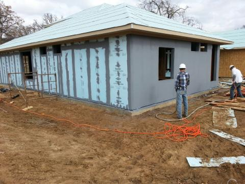 A water-resistant membrane that takes the place of house wrap is sprayed is painted over seams and window framing then sprayed over the entire wall to provide a weather-resistant air barrier.