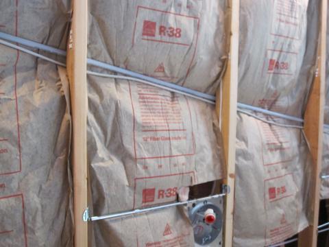 Faced fiberglass batt insulation incorrectly installed