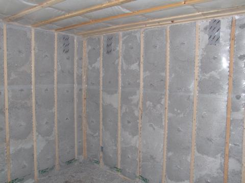 Blown cellulose insulation completely fills the netted wall and ceiling cavities