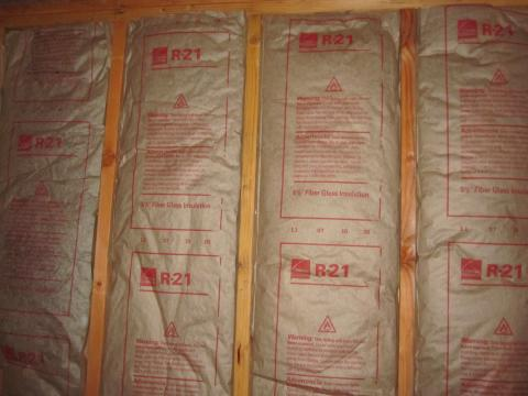 Faced fiberglass batt insulation can be stapled to the stud faces or slightly inset, but avoid compressing the batts