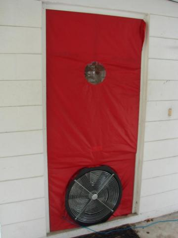 A blower door is installed in a doorway and is ready for testing