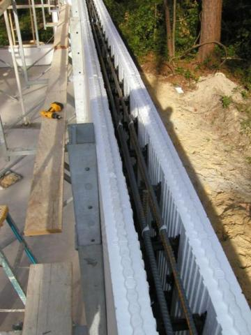 ICF bricks are stacked to form hollow walls that are reinforced with steel rebar before the concrete is poured in